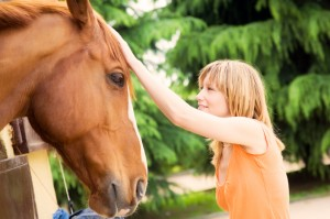 girl petting horse while volunteering